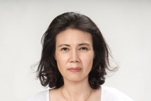 Portrait Of Beautiful Mature Asian Woman With Curly Hair Style Smiling With Joyful And Charming On White Background Isolate. Close Up Happy And Cheerful Older Lady Wear White Shirt Health Care Concept