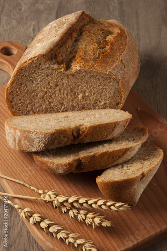 Foto op Plexiglas Brood Wheat bread on a wooden board