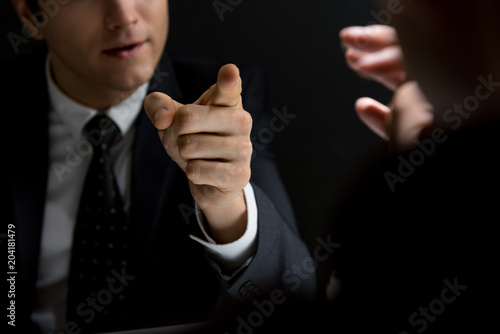 Angry official pointing hand to suspect and asking questions Wallpaper Mural