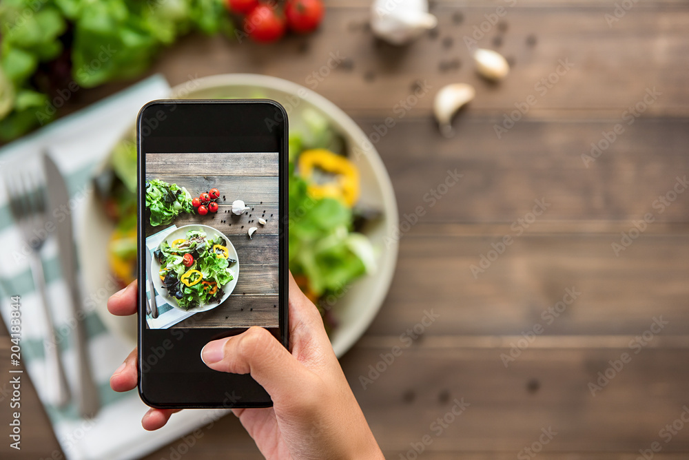 Fototapety, obrazy: Hand holding smartphone taking photo of beautiful food, mix fresh green salad on wood table, to share on social media