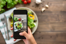 Hand Holding Smartphone Taking Photo Of Beautiful Food, Mix Fresh Green Salad On Wood Table, To Share On Social Media