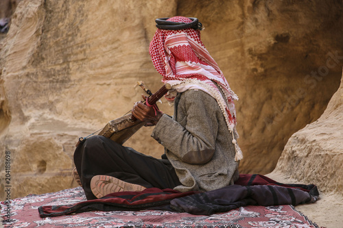 Photo Old bedouin in the keffiyeh plays on the national musical instrument of Jordan,P