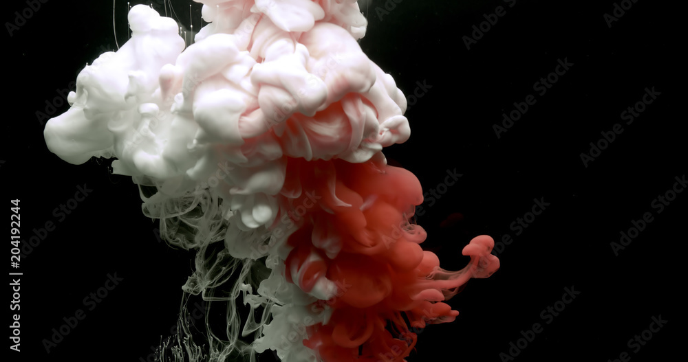 Photo  Red and white acrylic paint cloud spraying in water on black background