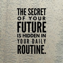 "Motivational Quote ""The Secret Of Your Future Is Hidden In Your Daily Routine."" On A Wooden Background."