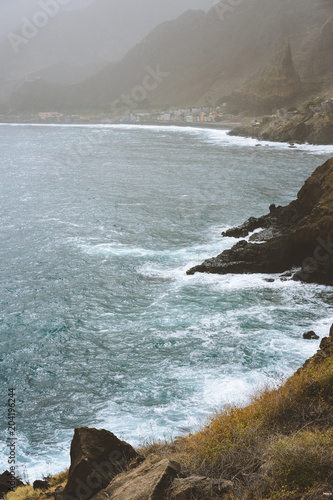Poster  Rough ocean waves with blowing spray rolling onto the rocky volcanic shore