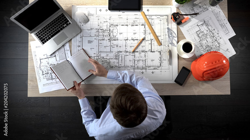 Fotografía  Architect checking notes making in his notebook to add it to drawing of building