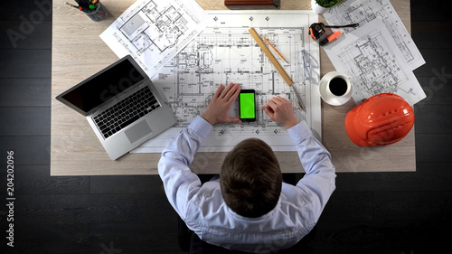 Developer checking information about house construction on green screen phone