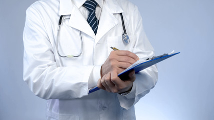 Professional physician writing in paper documents, keeping medical records