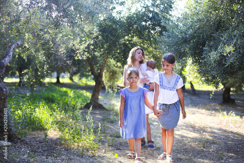 Photo Mother and three children in olive grove