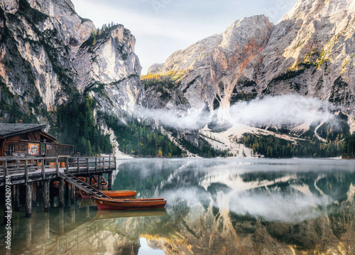 Poster Bergen Panoramic view of Braies Lake with the hut and boats in Dolomites mountains and Seekofel in the morning, Sudtirol, Italy