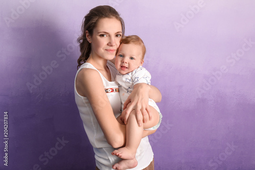 Fotobehang womenART Young mother with her cute little baby on color background