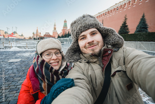 Poster happy romantic couple of tourists in warm clothes in winter makes a self-portrai