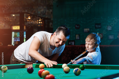 Photo Father and son play billiards