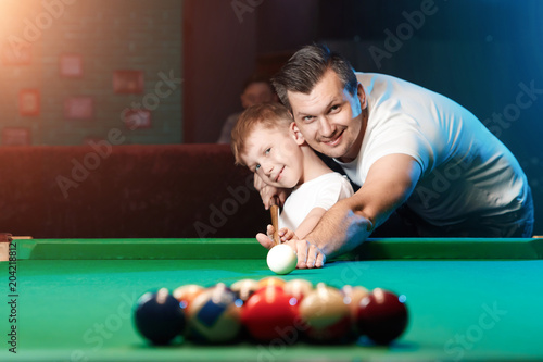 Tela Father and son play billiards