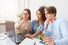 Three People Are Amazed. They Are Looking At The Laptops' Screen. Guy Is Holding A Credit Card.
