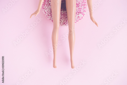 Flat lay of doll sitting on donut against pastel pink background. Poster Mural XXL