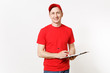 Delivery man in red uniform isolated on white background. Male in cap, t-shirt working as courier or dealer, holding pen, clipboard with papers, filling document, with blank empty sheet. Copy space.