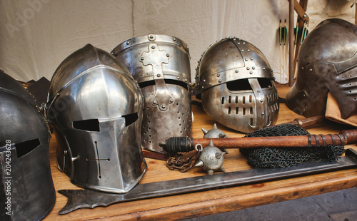 Shiny metal helmets of medieval knights with traditional weapons at a middle age Wallpaper Mural
