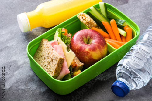 Foto Healthy school lunch box: Sandwich, vegetables ,fruit and juice on black stone