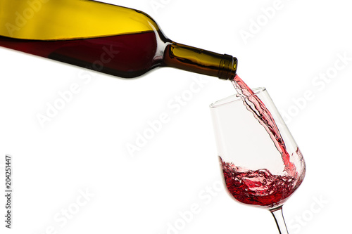 red wine pouring from bottle into glass on a white background. isolated.