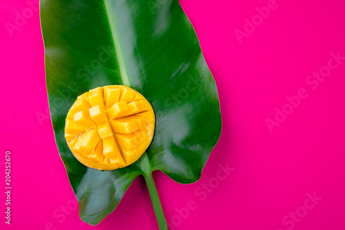Foto op Aluminium Roze Creative layout made of summer tropical fruits mango and tropical leaves on pink background. Flat lay. Copy space. Tropical food concept.