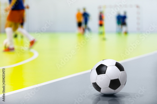 Indoor Soccer Futsal Ball. Indoor Soccer Match in the Background. Indoor Soccer Sports Hall. Sports Background. Youth Futsal League. Classic Soccer Ball.
