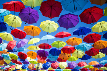 Fototapeta na wymiar Colorful umbrellas background. Coloruful umbrellas urban street decoration. Hanging Multicoloured umbrellas over blue sky. umbrellas with many colours.