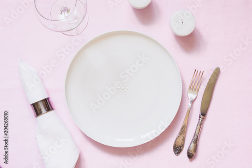 Table place setting on pink linen tablecloth. Top view. Concept.