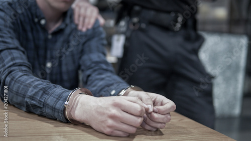 Fototapeta Criminal arrested and handcuffed while police grab shoulders.