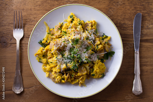 Scrambled eggs with pancetta, spinach, onion and parmesan. Omelette. View from above, top
