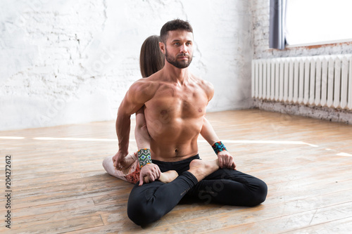 Young couple meditating together, woman and man sitting back to back on lotus pose on windows background. Yoga group concept.