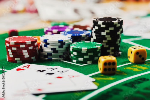 Cards on green felt casino table. Poker chips on table in casino плакат