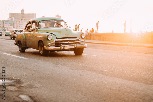 Foto op Canvas Retro Vintage car driving down road in sunset