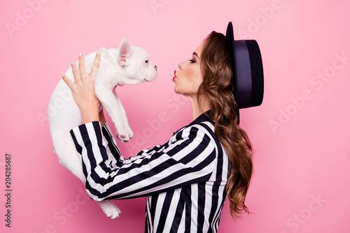 widok-z-boku-pol-twarzy-portret-profilowy-atrakcyjnej-ladnej-uroczej-dziewczyny-podnoszacej-psa-przed-twarza-dmuchanie-pocalunkiem