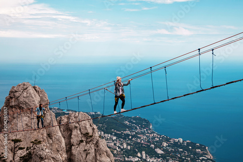 Fotografia  Young woman crossing the chasm on the rope bridge