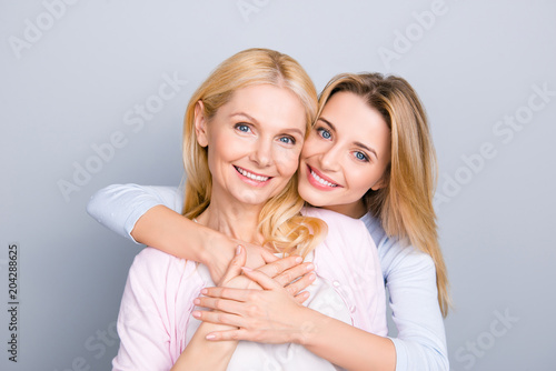Fototapeta Portrait of stylish cute attractive charming mother and daughter, family with one single parent, warm hugs, looking at camera isolated on grey background obraz