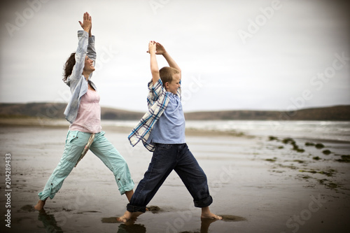 Foto op Canvas Strand A mother and a son are exercising on a beach.
