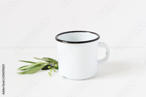 Styled stock photo. Feminine still life composition with blank white metal coffee enamel mug and green olive branch on white table background. Summer rustic scene, product mockup.