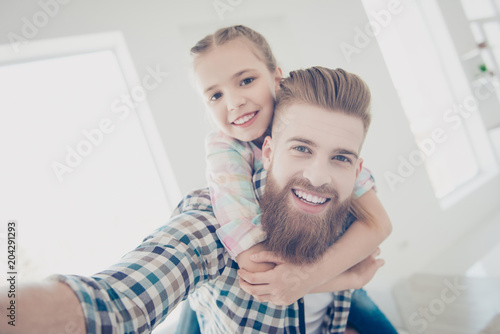 Fotografía  Self portrait of cheerful stylish father with red hair carrying on back cute lit