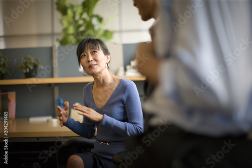 Mid-adult business woman sitting at a desk listening to colleagues in an office.