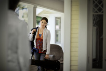 Young Woman Holding A Violin Case While Arriving On The Porch Of A House.
