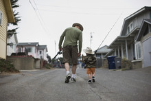 Rear View Of Father And Son Walking On Street With Fishing Rods