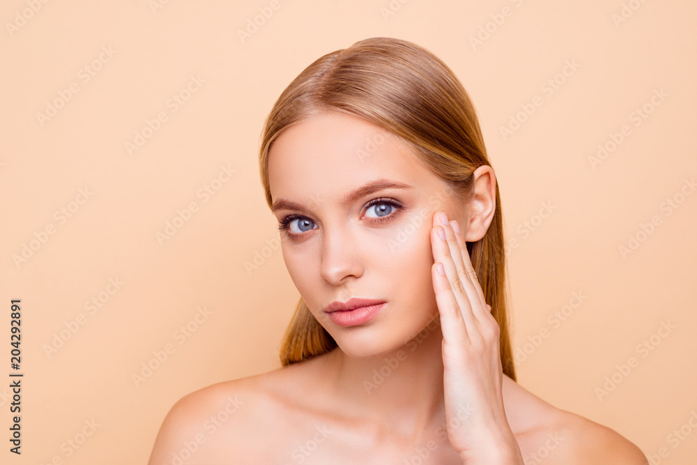 Fototapeta Portrait of pretty, charming, cute girl with smooth soft oiled dry skin touching cheek with fingers isolated on beige background wellness wellbeing concept, she need cream lotion mask peeling vitamins