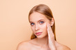 Portrait of pretty, charming, cute girl with smooth soft oiled dry skin touching cheek with fingers isolated on beige background wellness wellbeing concept, she need cream lotion mask peeling vitamins