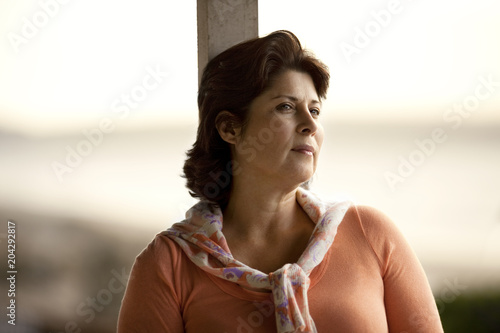 Mature woman gazing thoughtfully into the distance.