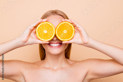 Fototapeta Joyful attractive charming cheerful toothy funny comic positive nude natural girl with beaming smile making binoculars with two pieces of orange, closing eyes, isolated on beige background obraz