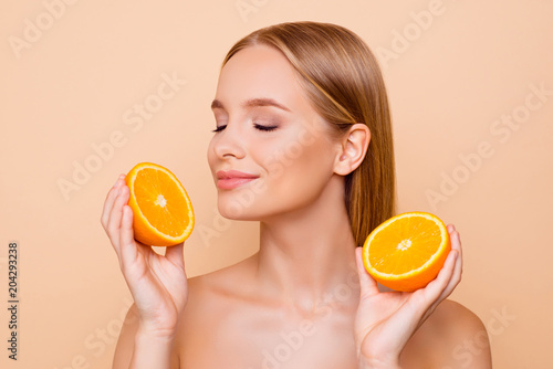 Fototapeta Portrait of joyful attractive pretty charming cheerful cute nude lovely dreamy natural girl having two pieces of orange, enjoying smell freshness with close eyes, isolated on beige background obraz