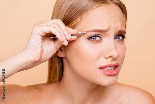 Photo Patient, pretty, nude, natural model looking at camera plucking eyebrows with tw