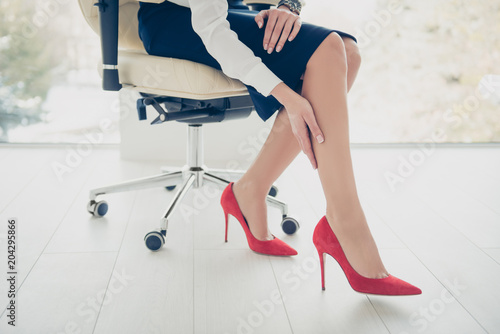 Obraz Cropped portrait bottom view of woman's legs wearing black skirt red high heel shoes sitting on armchair touching her perfect smooth soft legs with hand having trouble dry skin, health care concept - fototapety do salonu