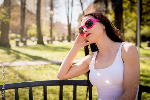 Photo Thoughtful woman sitting on a bench in pink sunglasses